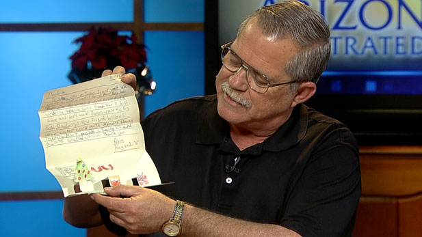 Stuart Love shows one of the letters he and other Operation Santa volunteers have answered.