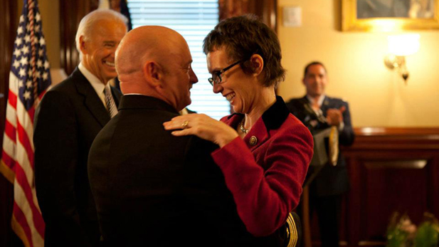 U.S. Rep. Gabrielle Giffords, still recovering from a bullet wound to the head, congratulates her husband, astronaut and Navy Capt. Mark Kelly, after he is honored by Vice President Joe Biden.