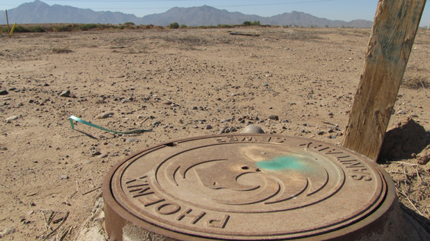 A solitary manhole cover marks a stalled development in suburban Phoenix.