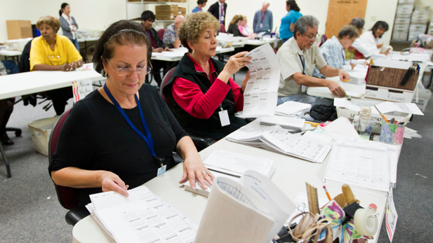 Pima County Elections Department workers process early ballots after the 2012 election.
