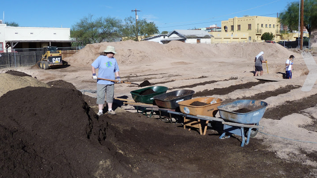Neighbors shovel rich soil for the first plots in Rincon Heights' community garden.