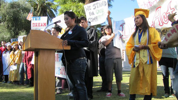 Arizona DREAM Act Coalition President Dulce Matuz, at lectern, and Team Awesome founding member Viri Hernandez, 21, in cap and gown.