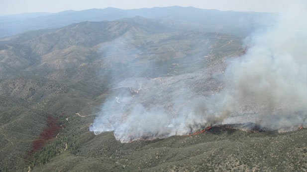 The Gladiator Fire near Crown King, AZ, burns along a ridge line; stain from fire retardant drop is at left.