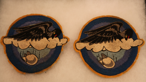 Two patches embroidered with evocative symbols: a bird in the clouds dropping a bomb. Is this a unit insignia?