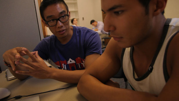 New Start participant Fernando Garcia (right), receives tutoring on writing papers for university classes.