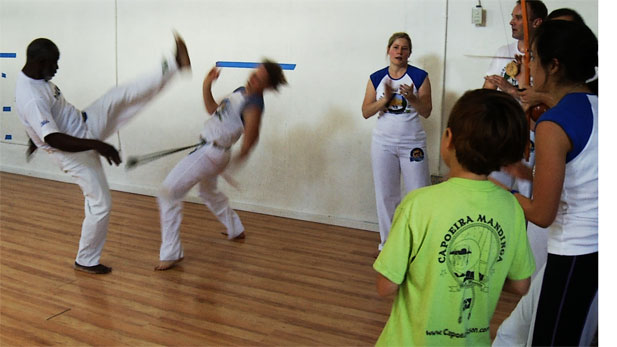 Anne Pollack and Mestre Lombão play capoeira during an roda