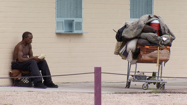 Homeless man reading near Santa Rita park.