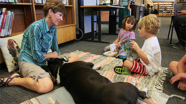 "The ""Read to a Dog"" program at the Pima County public libraries uses therapy dogs as a way to promote literacy among children."