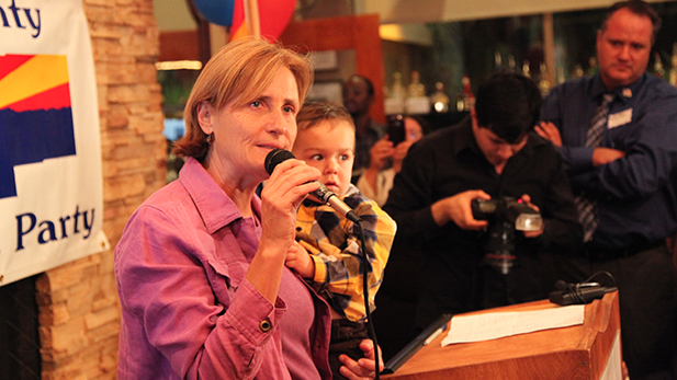 Tucson City Council member Karin Uhlich, holding her foster son Isaiah, at the Democratic Party gathering on election night, Nov. 5, 2013.