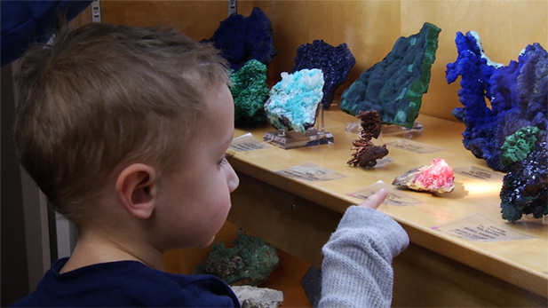 A young visitor looks at different minerals at The University of Arizona's Mineral Museum.