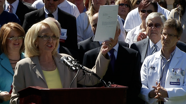 Gov. Jan Brewer shows off her 7-page Medicaid expansion bill at March 12, 2013 state Capitol rally.