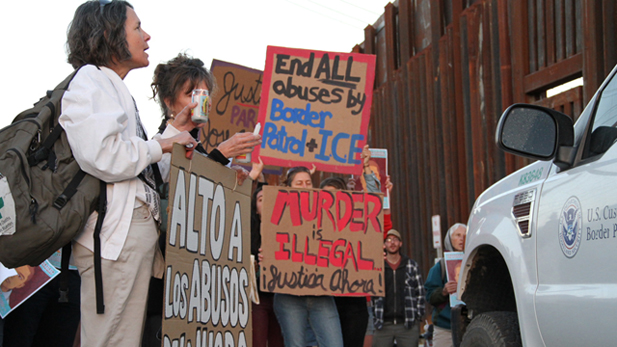 Protestors stand at the site where a 16-year-old boy was shot and killed on the Mexican side of the border by Border Patrol in October 2012.