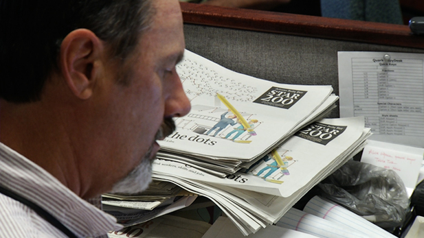 David Witchner, Assistant Business Editor with the Arizona Daily Star works at his desk.