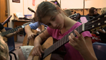 A student plays guitar along with her teacher and the rest of the class.