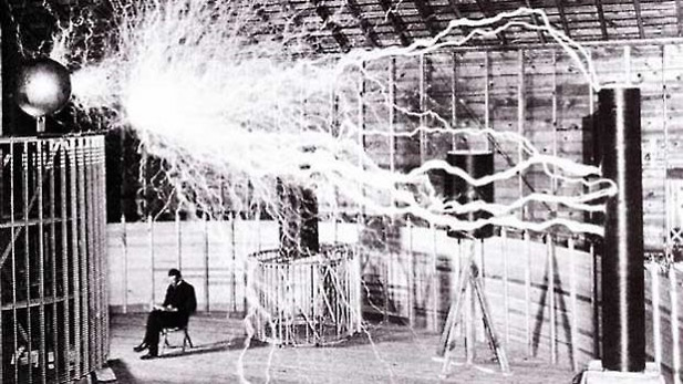 Publicity photo of Nikola Tesla sitting in his laboratory in Colorado Springs in December 1899. Tesla's notes identify the photo as a double exposure. Photo by Dickenson V. Alley of Century Magazine. (Wikimedia Commons)