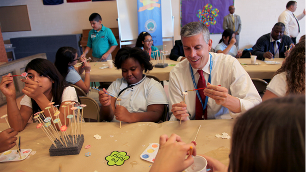 U.S. Secretary of Education Arne Duncan painting with Simone Ufondu, 11, at Dodge Middle School.