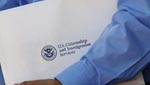 A new US citizen hold his US Citizenship and Immigration packet in his hands.