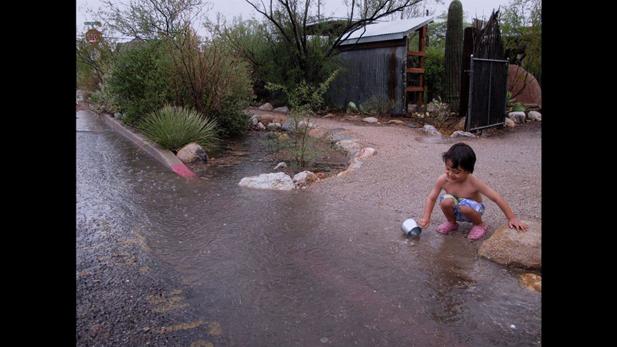 A child plays in the rain near a freshly filled rain water basin.