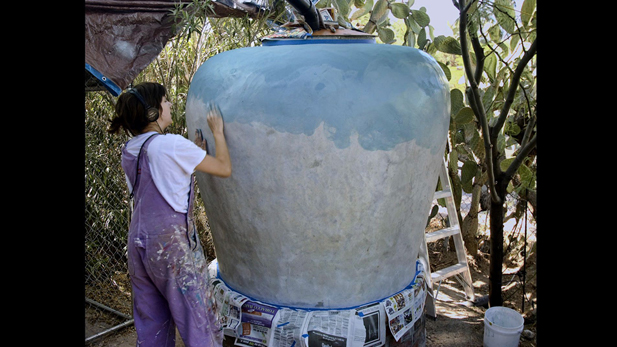 A local artists is in the beginning stages of painting a newly constructed rain jar.