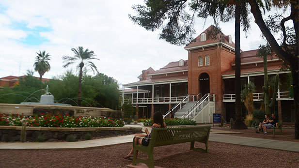 Students sit on benches at the front entrance of Old Main.