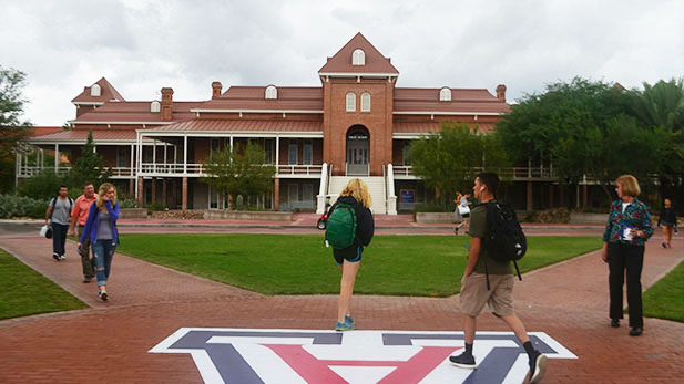 University of Arizona students walk by the Old Main.