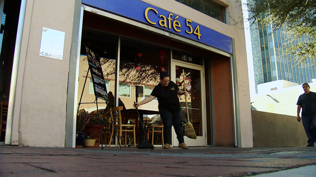 Cafe 54 employee and job coach Peggy Starr, sweeps the front of the cafe before they open their doors for the day.