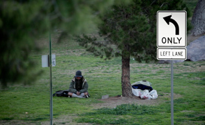 Homeless man sitting in Pancho Villa park.