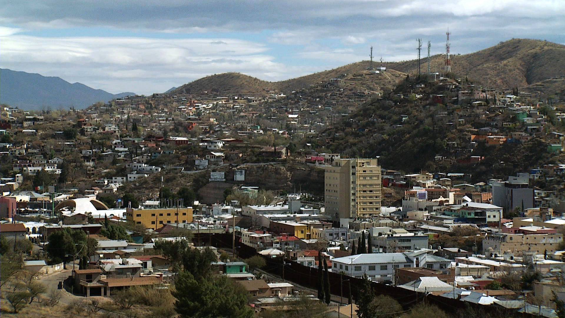 The border of Nogales, Arizona and Nogales, Mexico is separated by a large brown metal fence.