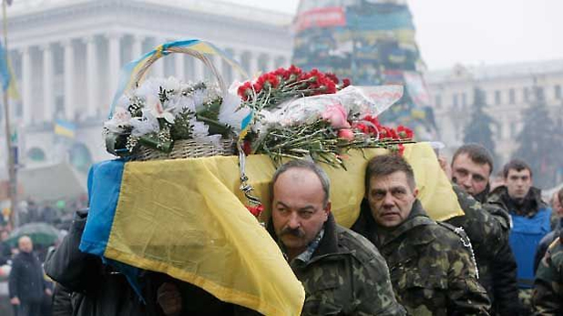 A coffin with the body of a protester killed in clashes with the police is carried through the crowd in Independence Square, Kiev, Monday, March. 3, 2014. (AP Photo/Efrem Lukatsky)