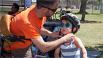 A father and his child gear up for bike safety and to enjoy the events of Cyclovia Tucson, an event which will be comprised of multiple event, giveaways and prizes