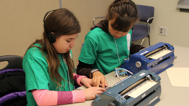 Beatrise Silva (left) and Evamaria Tanori Contreras, both 11, practice on a Victor Reader Stream device before taking the speed and accuracy portion of the Braille Challenge.