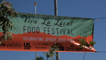 A banner for the very first Viva la Local Food Festival hangs high above the even grounds.
