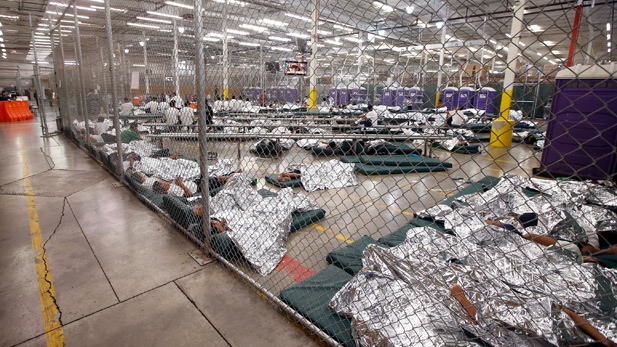 Children sleep on mattresses without pillows, covered with foil blankets.