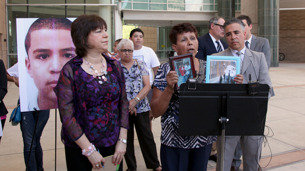 Taide Elena, Jose Antonio's grandmother, shows a photo of the teen next to an image of his coffin at the border.