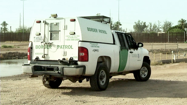 A Border Patrol vehicle parked near the US / Mexico border fence.