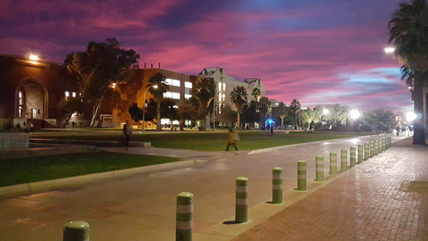Students walk across the UA Mall as the sun sets in the background. Photo taken December 10th, 2015.