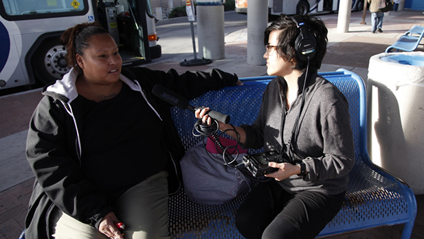 Christina Hamaley talks about her life in Tucson while waiting for a bus at Roy Laos Transit Center. Pictured with producer Sophia Paliza-Carre.