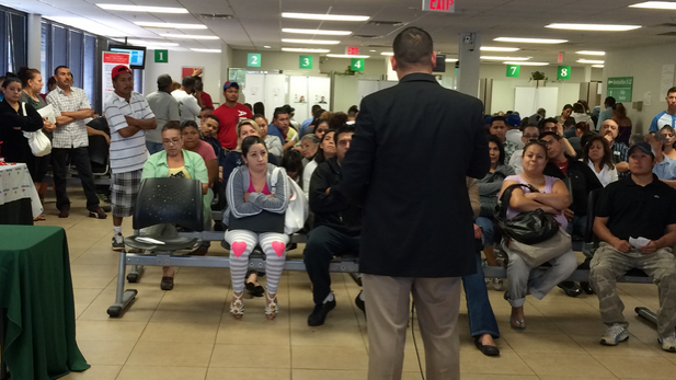 Border Patrol Agent George Trevińo speaks to Mexican immigrants at the Mexican consulate in Phoenix.