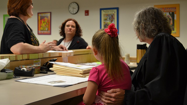 Family Drug Court Judge Susan Kettlewell (right) and her granddaughter listen to discussion on a family reunification.
