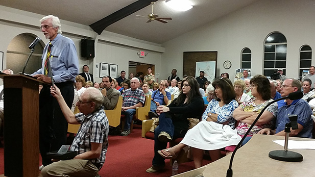 St. David resident Don Buchanan (left) addresses the Benson City Council in front of a packed house Monday night, speaking against the Villages at Vigneto due to concerns over water use.