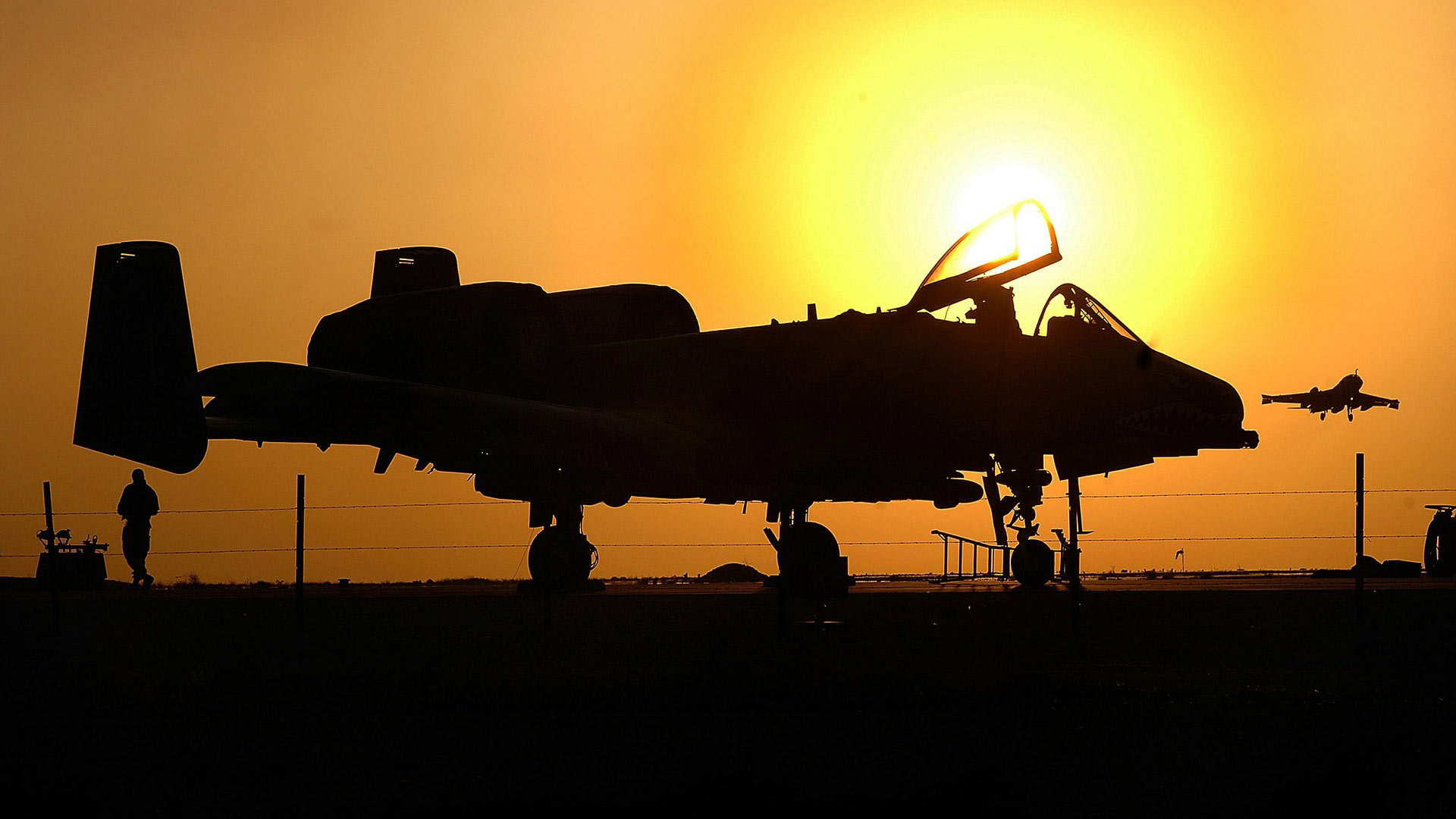 An A-10 aircraft silhouetted by the setting sun.