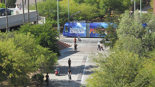 A modern streetcar leaves the Highland Ave. stop near the University of Arizona.