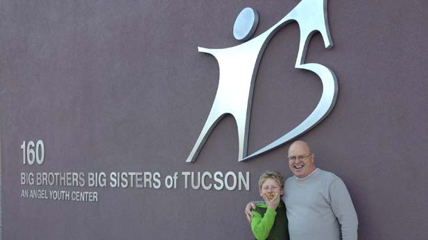A different pair of Big / Little Brothers, Ian and John, in front of the BBS sign at the group's Tucson headquarters.