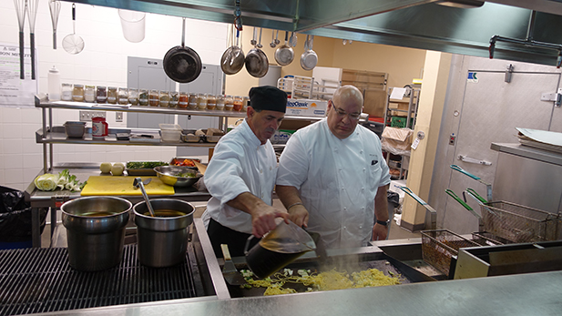 Chef Michael Omo (right) helps prep food in the Arizona Room, a campus restaurant.