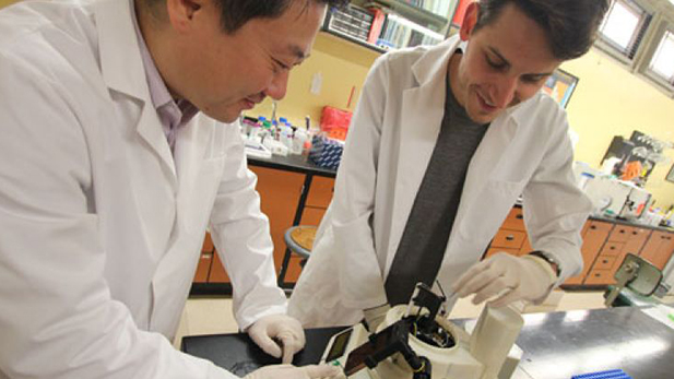 Jeong-Yeol Yoon and Dustin Harshman work on the infection diagnostic device.