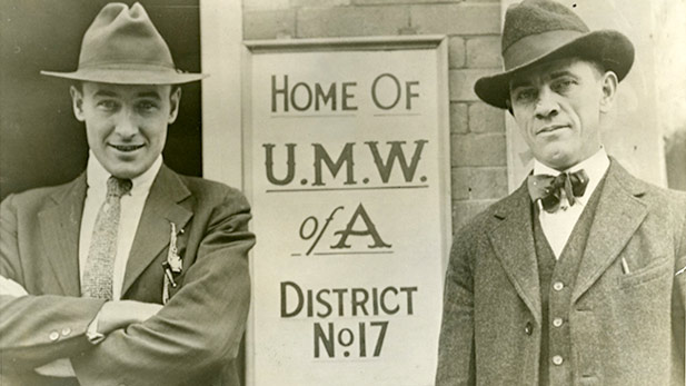 Frank Keeney and Fred Mooney pose next to a UMWA sign in Charleston, WV (1915).