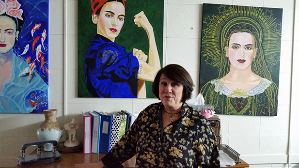 Yolanda Soto, CEO and President of Borderlands Food Bank, in her office in Nogales. The bright paintings on her walls were all done by an inmate who works for Borderlands as part of a labor force program. (She's a big fan of Kahlo's.)