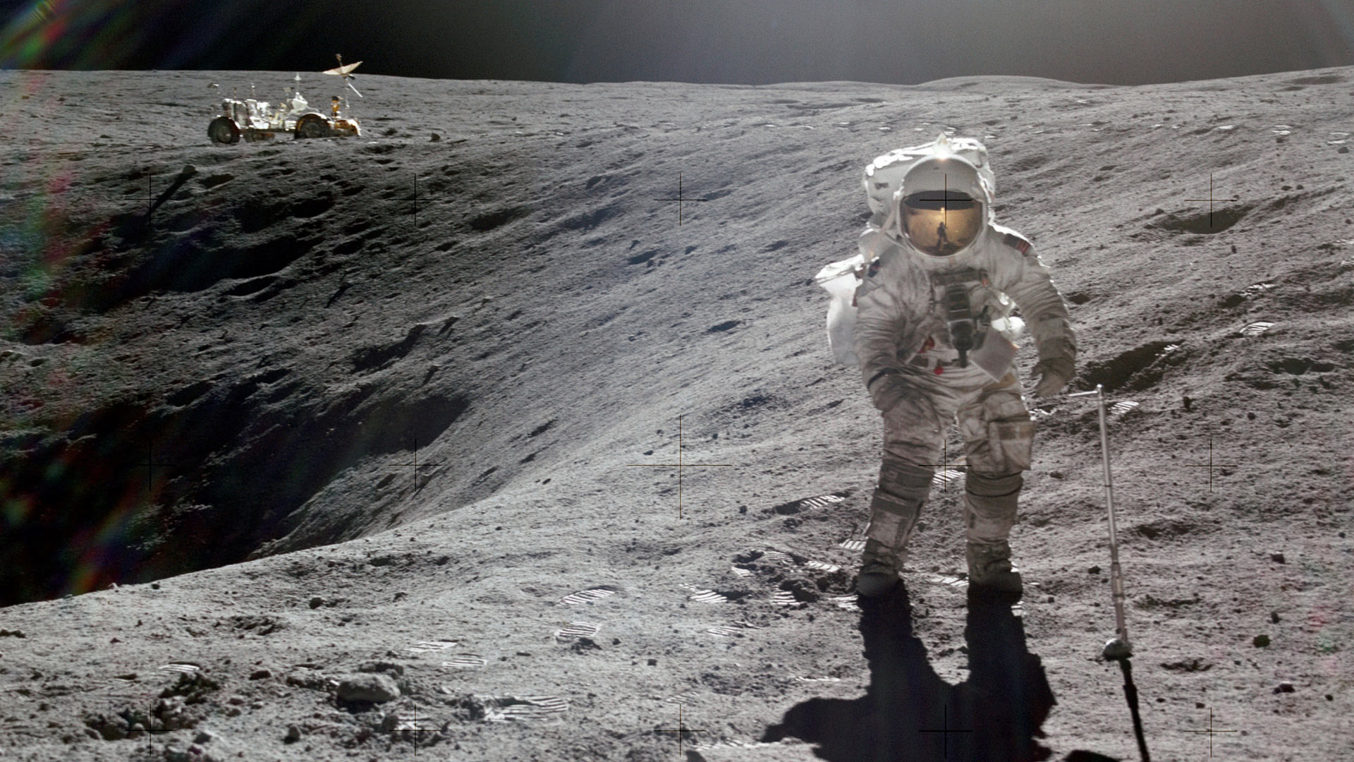 Astronaut Charles M. Duke Jr., lunar module pilot of the Apollo 16 lunar landing mission, is photographed collecting lunar samples at Station no. 1 during the first Apollo 16 extravehicular activity at the Descartes landing site. This picture, looking eastward, was taken by Astronaut John W. Young, commander. Duke is standing at the rim of Plum crater, which is 40 meters in diameter and 10 meters deep. The parked Lunar Roving Vehicle can be seen in the left background.