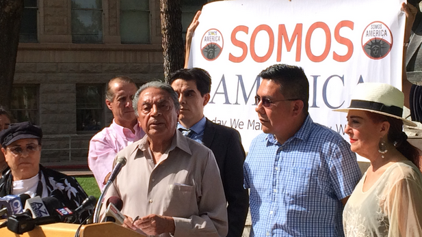 Roberto Reveles, at microphone, and other Somos America members announce the possibility of a renewed boycott over immigration legislation.