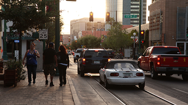 People walk along the streetcar route in downtown Tucson on April 5, 2016.